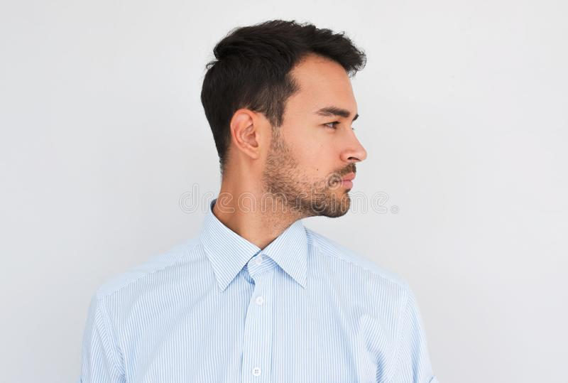 Profile view of handsome young handsome male wearing light blue shirt looking to the copy space for advertisement, posing on white royalty free stock image