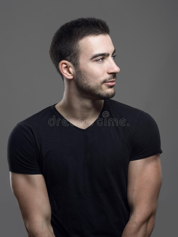 Profile view of happy confident young fit man in blank black shirt looking away stock images