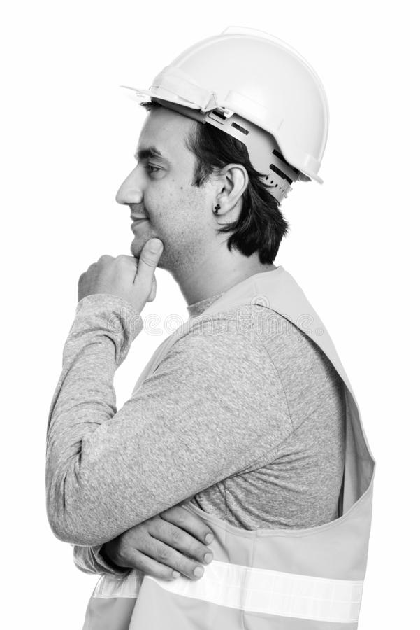 Profile view of happy Persian man construction worker smiling and thinking. Studio shot of Persian man construction worker isolated against white background in stock image