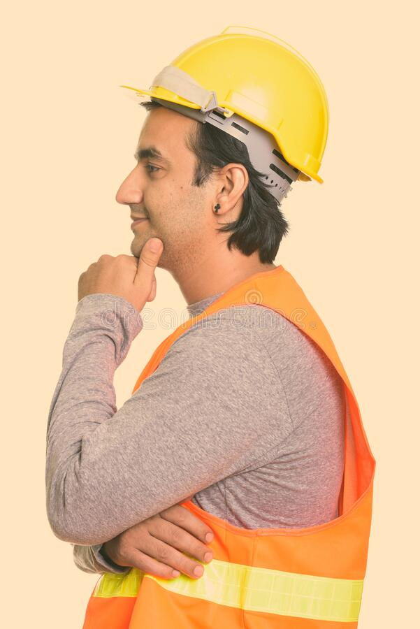 Profile view of happy Persian man construction worker smiling and thinking royalty free stock image