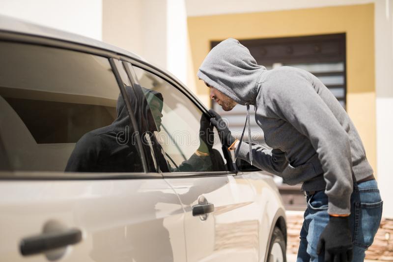 Stealing personal belongings. Profile view of a man wearing a hoodie and looking through a car window trying to steal personal belongings royalty free stock photography
