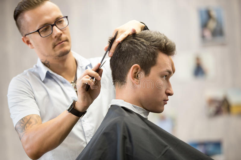 Profile view portrait of attractive young man getting haircut stock images