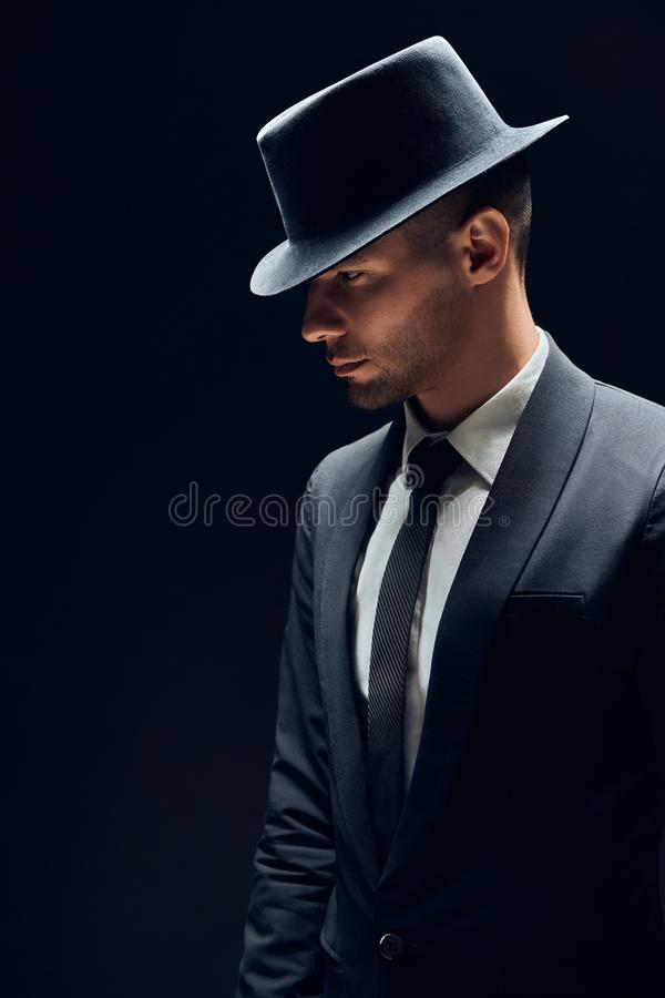 Profile view portrait oh handsome man in black suit and hat on dark background stock images