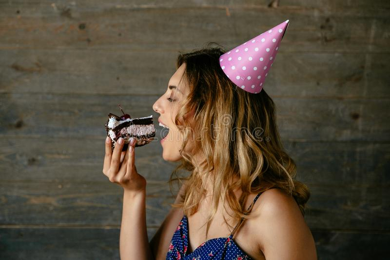 Profile view of pretty woman eating piece of birthday cake. Attractive woman eating a cream chocolate cake, celebrating birthday party, wearing holiday hat royalty free stock photo