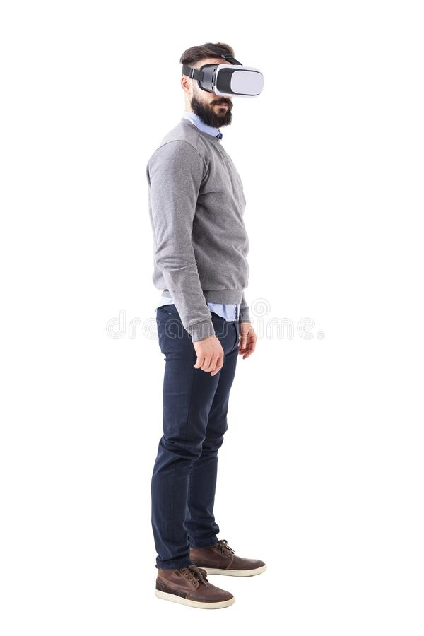 Profile view of serious bearded smart casual man using virtual reality glasses. royalty free stock image