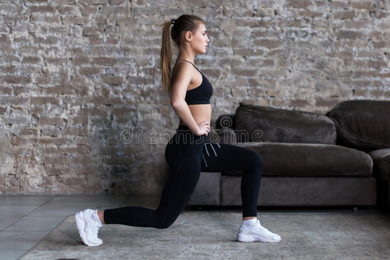 Profile view of sporty girl doing lunges working-out leg muscles and glutes in loft interior.  royalty free stock image