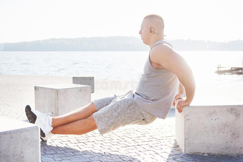 Profile view of a strong man exercising his arms and doing tricep dips outdoors in a park bench.  stock photo
