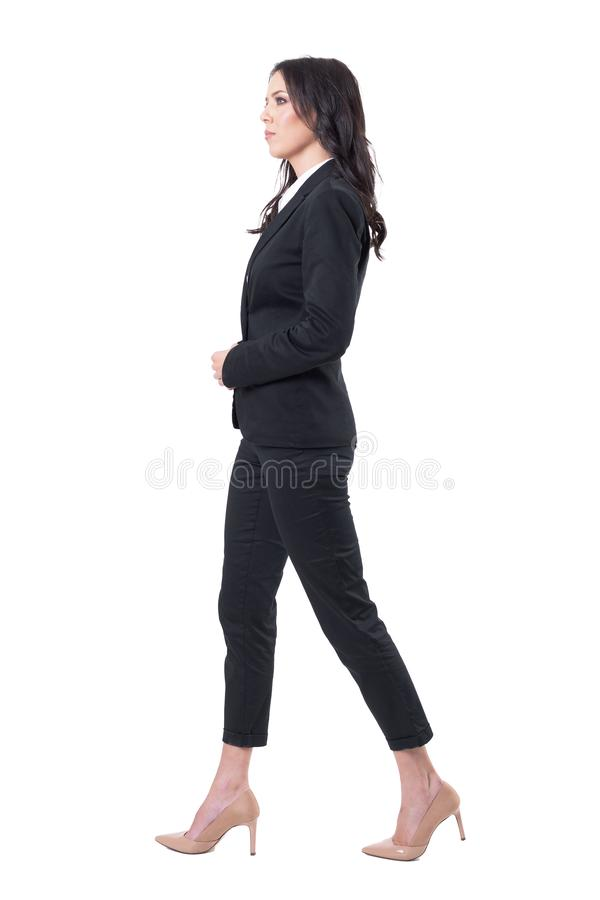 Profile view of successful female ceo in black suit walking and looking forward. royalty free stock image