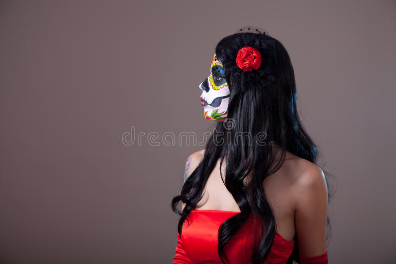 Profile view of Sugar skull girl in red dress royalty free stock photo