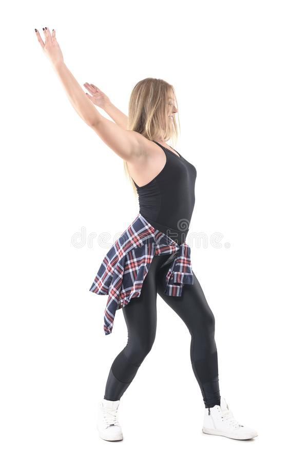 Profile view of woman in street style modern clothes dancing with arm raised up. Full body length portrait isolated on white background royalty free stock images