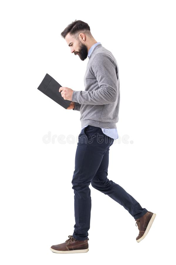 Profile view of young bearded businessman walking while reading notebook or planner. stock image