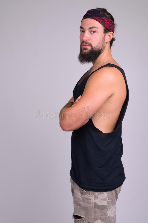 Profile view of young bearded handsome rebellious man looking at camera stock photo