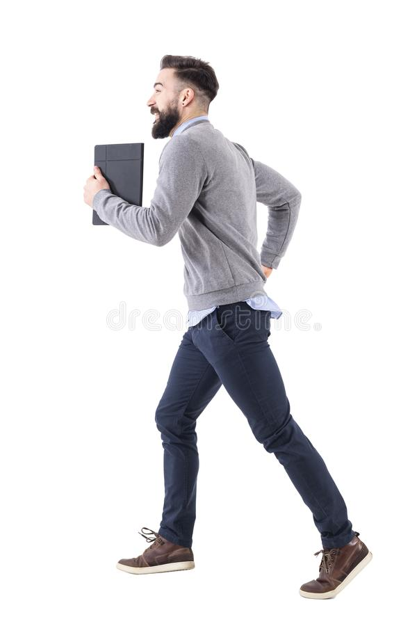 Profile view of young businessman with notebook running. Deadline concept. royalty free stock photography