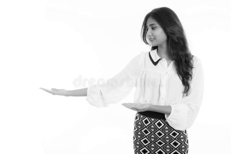 Profile view of young happy Persian businesswoman smiling while showing something stock photography