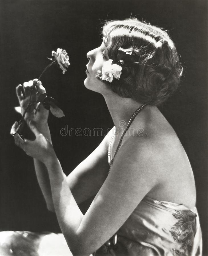Profile view of young woman smelling flower stock photography