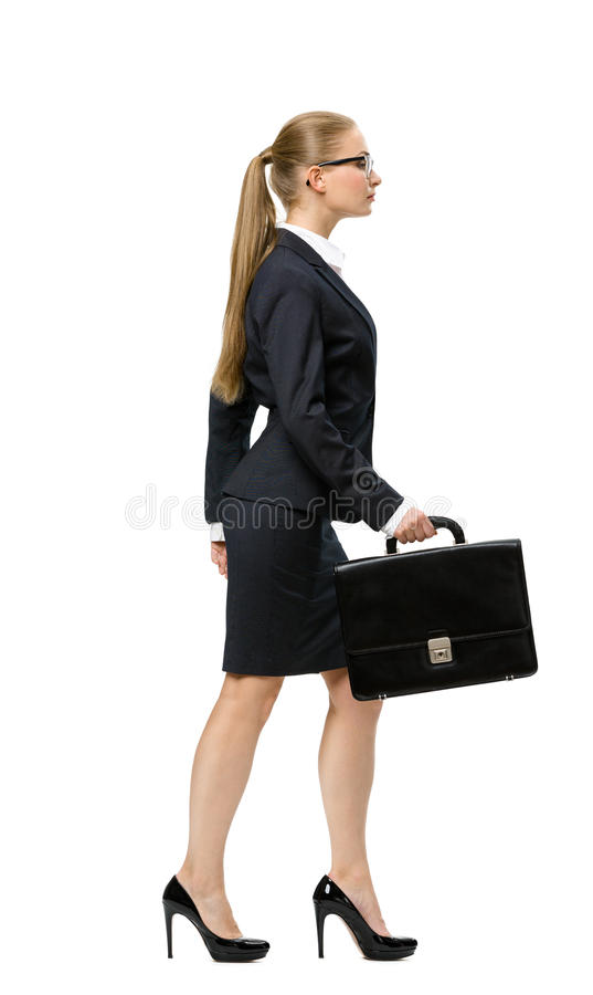Profile of walking business woman with case royalty free stock image