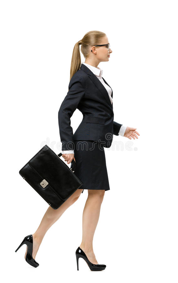 Profile of walking businesswoman with case royalty free stock photos