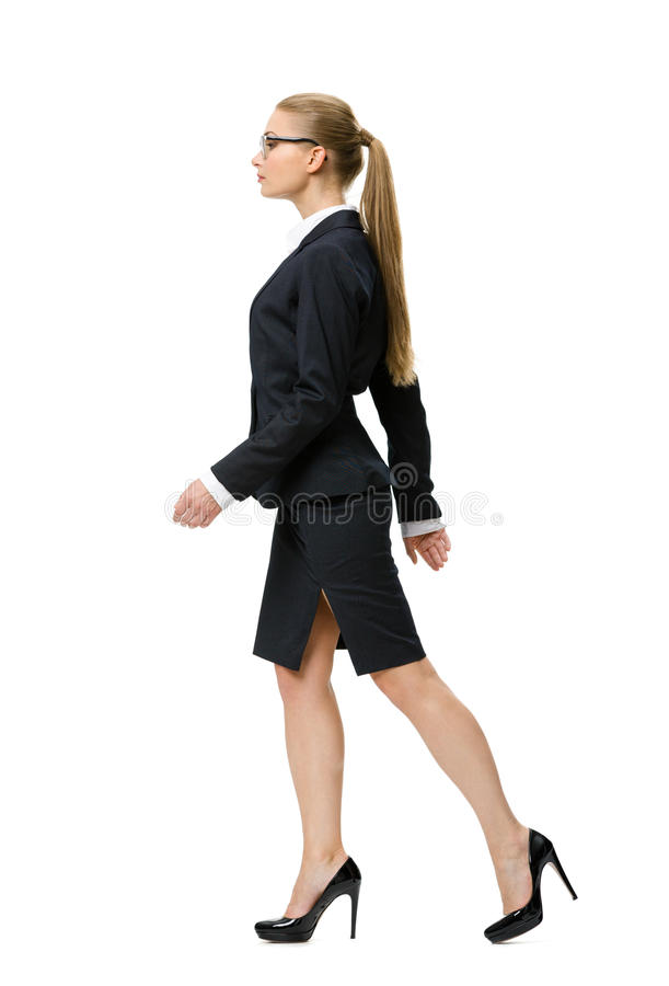 Profile of walking businesswoman. Isolated on white. Concept of leadership and success stock photos