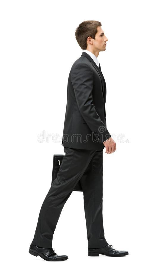 Profile of walking with case businessman stock photo