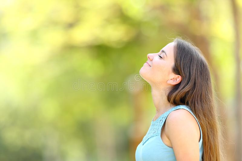 Profile of a woman breathing fresh air in a forest stock image