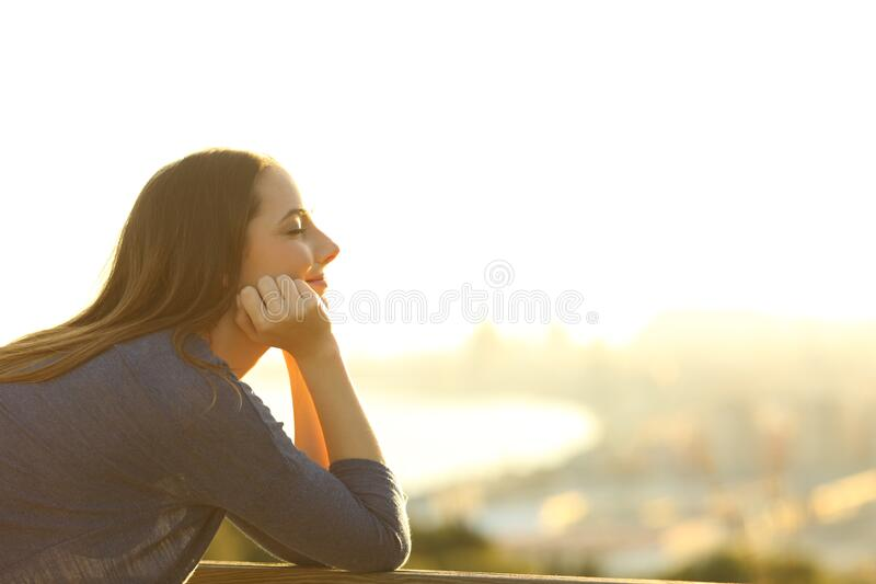 Woman with eyes closed relaxing at sunset stock photography