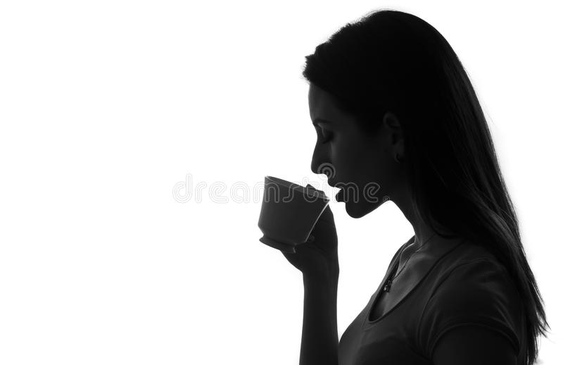 Profile of woman holding and drinking cup of coffee or tea black and white isolated stock photo
