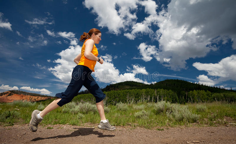 Profile of woman jogging on trail with sky and clo stock photos