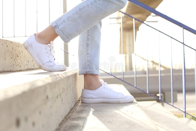 Profile of woman legs wearing sneakers walking down stairs stock photography