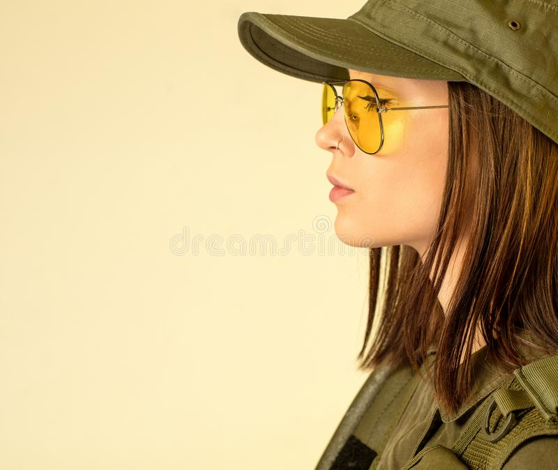 Profile of woman`s in soldier`s suit on yellow background.  royalty free stock images