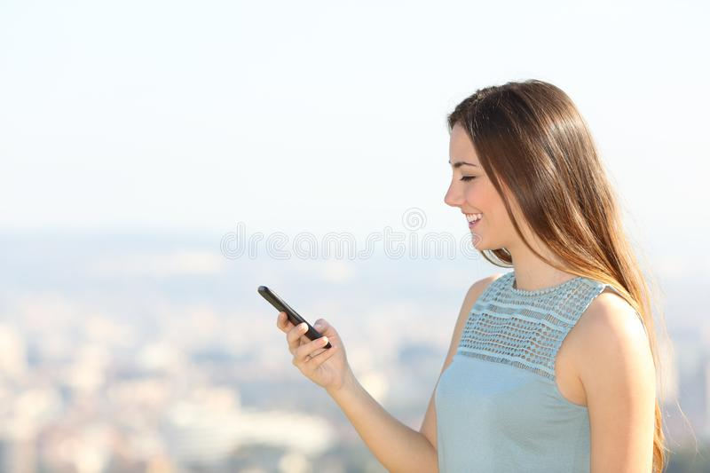 Profile of a woman using smartphone in the city outskirts stock photography
