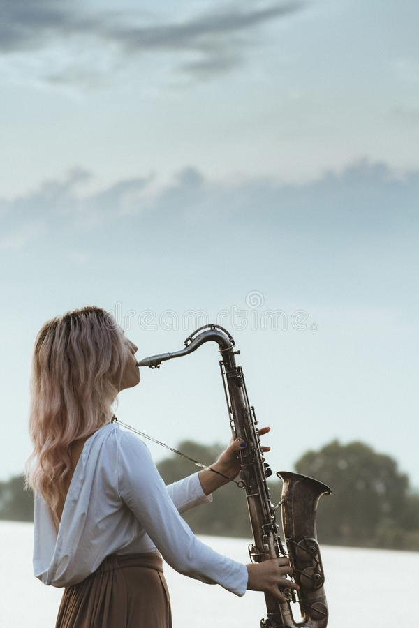 Profile of a young beautiful girl playing the saxophone against a cloudy sky, a woman relaxes on nature, music and hobby concept stock photos