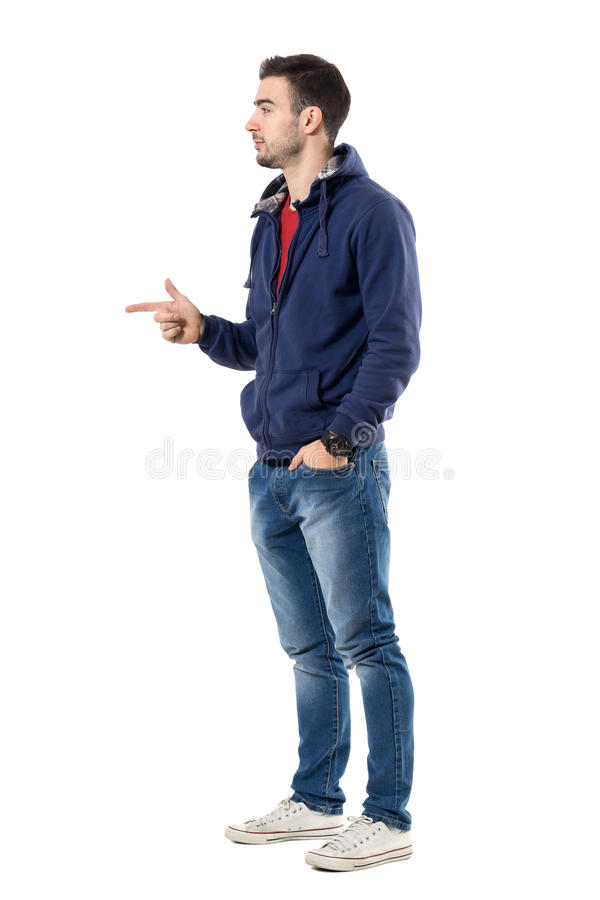 Profile of young casual guy in sweatshirt pointing finger showing copyspace. Full body length portrait isolated over white studio background stock images