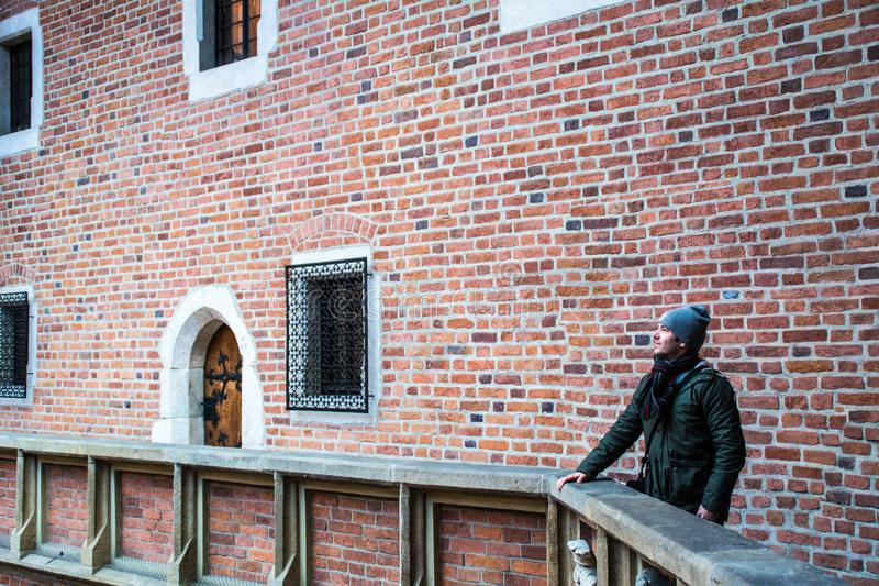 Young boy profile at winter, Collegium Maius walls, Cracow, Poland. Profile of a young and cheerful boy at winter season contemplating the walls of Collegium stock image