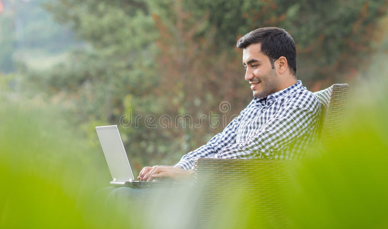 Profile of a young man with laptop stock photography