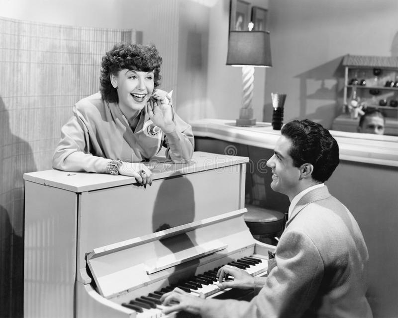 Profile of a young man playing a piano with a young woman standing in front of him and smiling and singing royalty free stock image