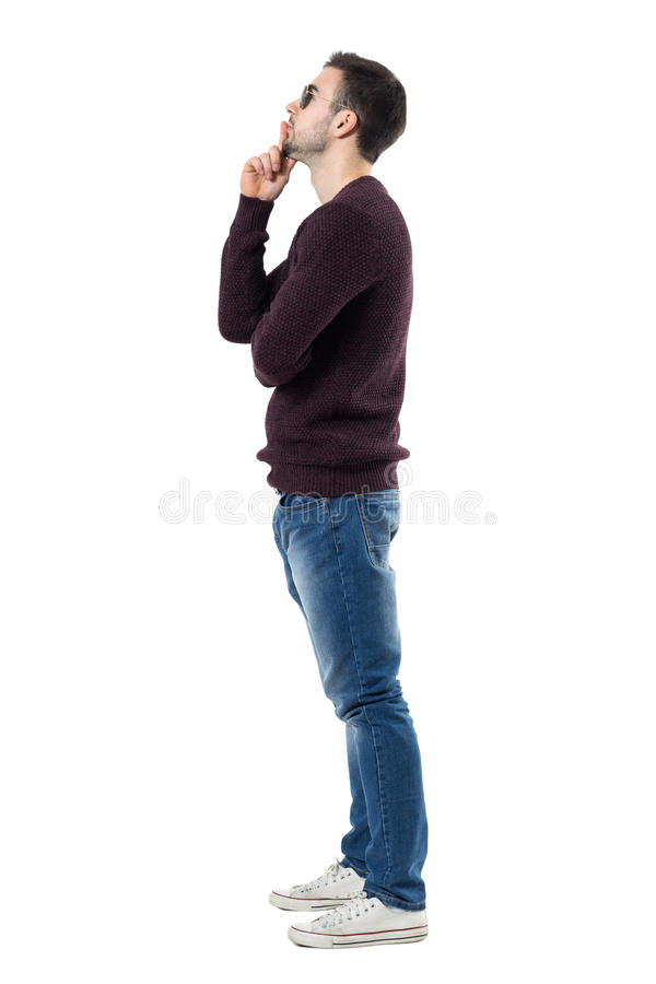 Profile of young man wearing maroon pullover and sunglasses thinking and looking up. Full body length portrait isolated over white studio background royalty free stock photography