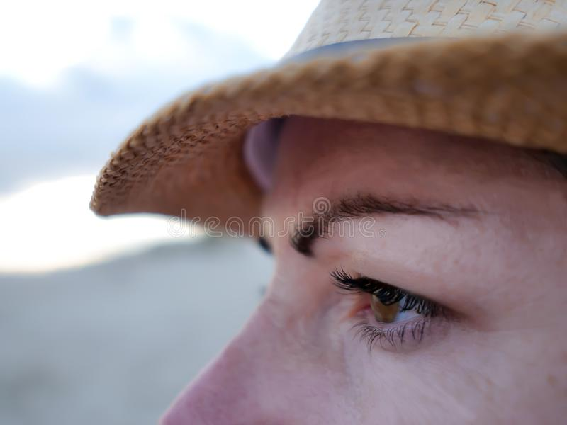 Profile of a young woman in a hat looking to the side, close-up royalty free stock images