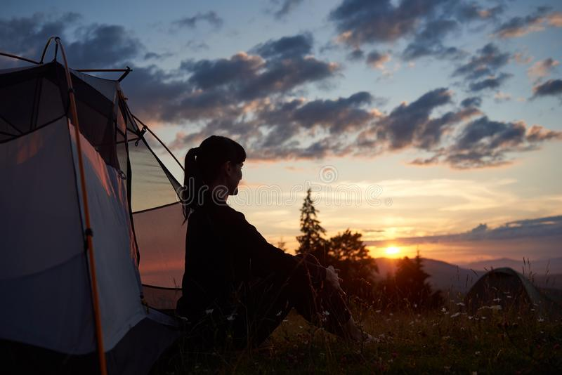 Profile of young woman sitting in tent in grass and fieldflowers on top mountain with view of rising sun. Profile silhouette of young woman sitting in tent in stock images