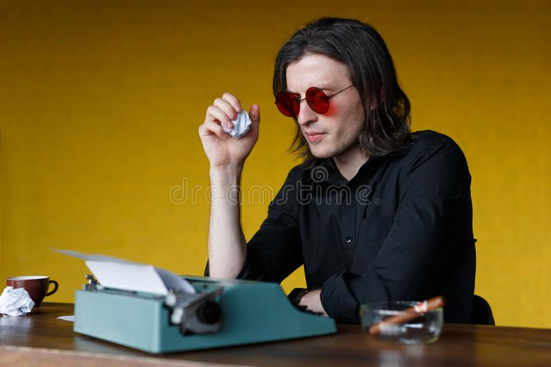 Profile of a writer sitting at table working on a typewriter, crumpled sheets of paper, over yellow background. stock images
