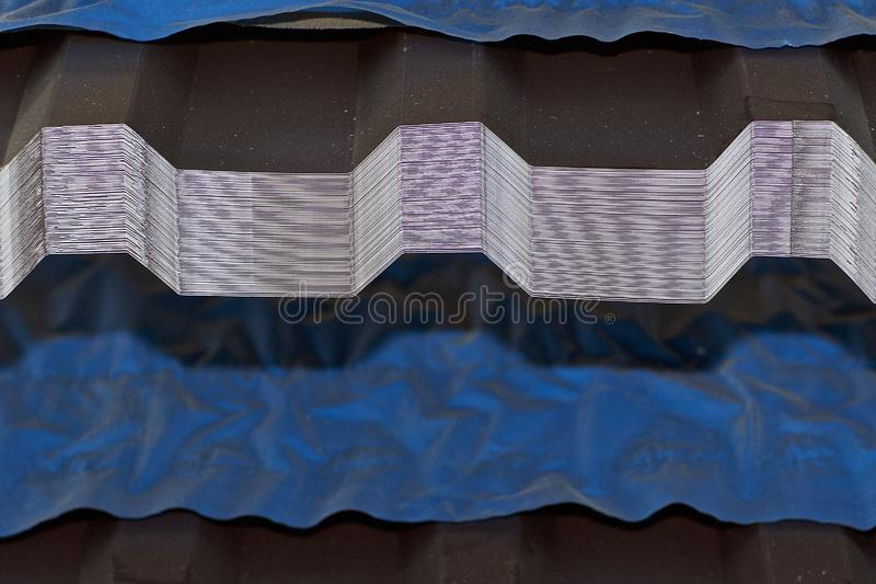 Profiled galvanized sheet with polymer coating in packs in the warehouse of metal products royalty free stock image