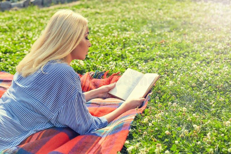 Profilen av den blonda flickan läste boken på grönt gräs arkivfoto