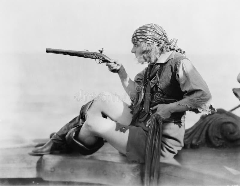 Profilen av en ung kvinna som rymmer en flintlockpistill i a, piratkopierar dräkten (alla visade personer inte är längre uppehäll royaltyfri fotografi