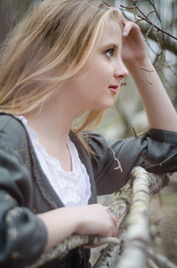 Profilera bilden av den blonda flickan som trycker på hennes huvud arkivfoto