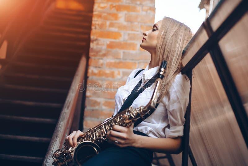 Profilera den unga attraktiva flickan för ståenden i den vita skjortan med en saxofon - som är utomhus- i gammal stad Sexig ung k arkivbild