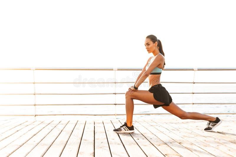 Profilera fotoet av den slanka sunda kvinna20-tal i träningsoverallen som squatting, arkivbilder