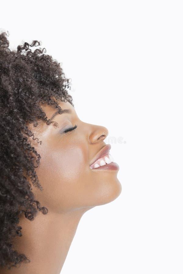 Profilera sikten av en afrikansk amerikankvinna som ler med ögon som stängs mot grå bakgrund arkivfoto