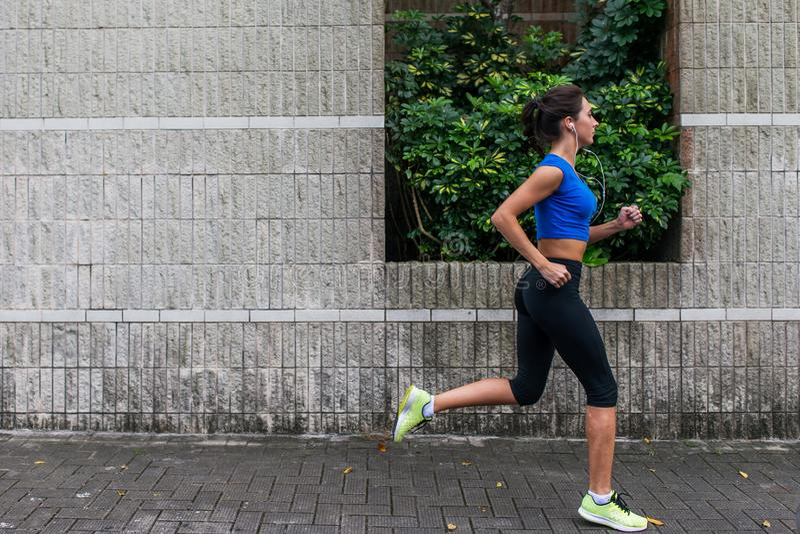 Profilera sikten av en sportig ung kvinna som utomhus utarbetar Konditionflickaspring på trottoaren royaltyfria bilder