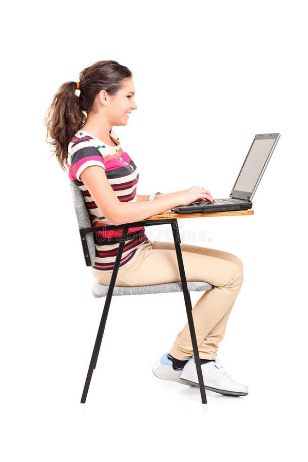 Profilera skottet av en skolflicka som arbetar på bärbara datorn fotografering för bildbyråer