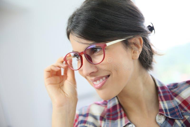 Profilera ståenden av att le bärande glasögon för den unga kvinnan royaltyfria bilder