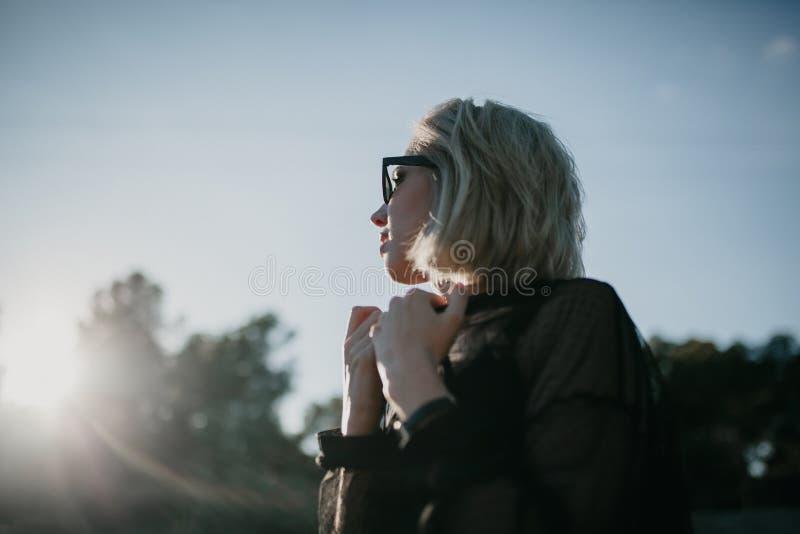 Profilera ståenden av den blonda flickan som utomhus ser solen i natur arkivbilder